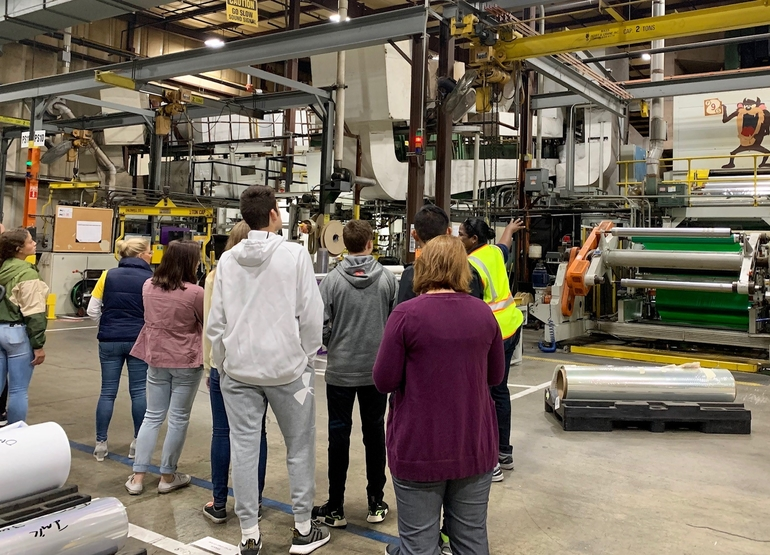 Kesha Smith, a production group supervisor at FLEXcon, gives a tour of its Gardner facility to David Prouty High School students.